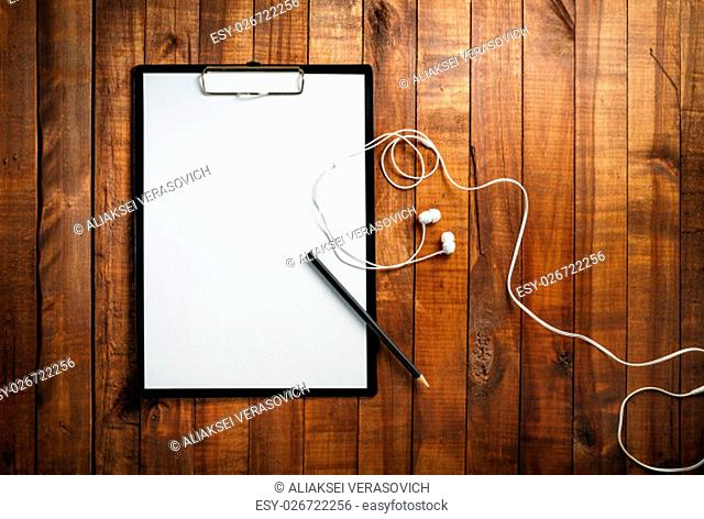 Blank clipboard on vintage wooden background. Clipboard with a blank sheet of white paper, pencil and headphones. Mock-up for branding identity for designers