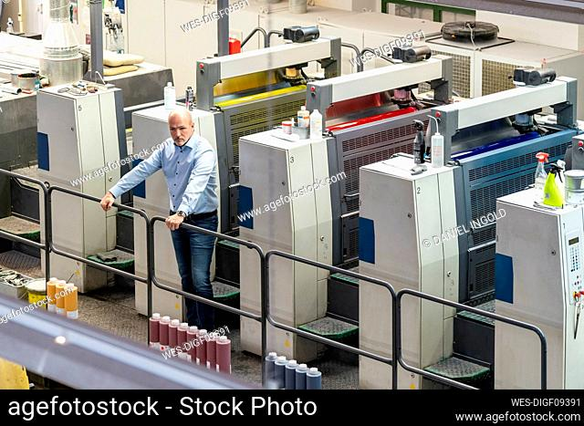 Businessman standing at machines in a printing plant