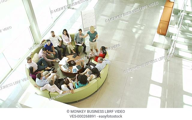 Elevated view as motivational speaker stands by flipchart and encourages businessman to write down ideas which his colleagues applaud