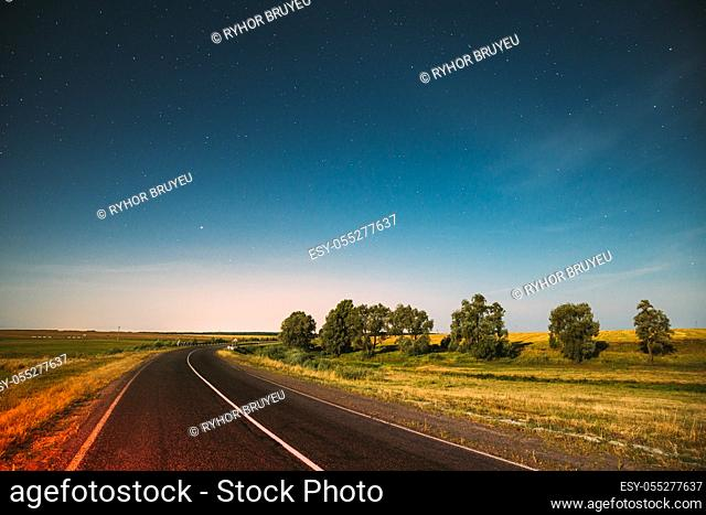 Blue Night Starry Sky Above Country Asphalt Road In Countryside And Green Meadow. Night View Of Natural Glowing Stars