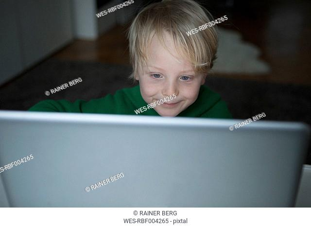 Portrait of smiling blond boy looking at computer