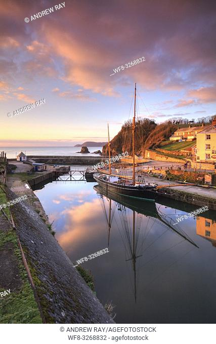 Sunrise reflected in the historic harbour at Charlestown near St Austell on the south coast of Cornwall
