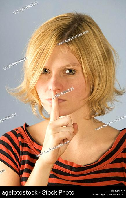 Teenager holds index finger to mouth, 21 years, gestures, Austria, Europe
