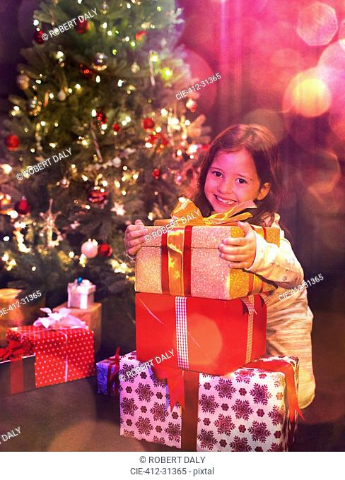 Portrait smiling girl with stack of Christmas gifts