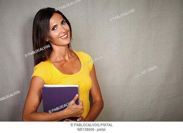 Charismatic young woman holding mobile technology while smiling - copy space