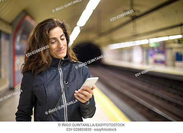 smiling woman with blue coat, in urban subway or underground of Madrid city, using and typing mobile smart phone,
