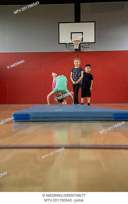 Girl doing somersault on exercise mat in sports hall with her friends, Munich, Bavaria, Germany