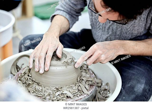 A man seated at a potter's wheel working and shaping a clay pot by removing excess clay