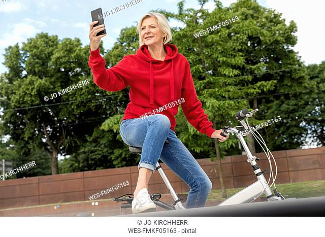 Senior woman with city bike using cell phone