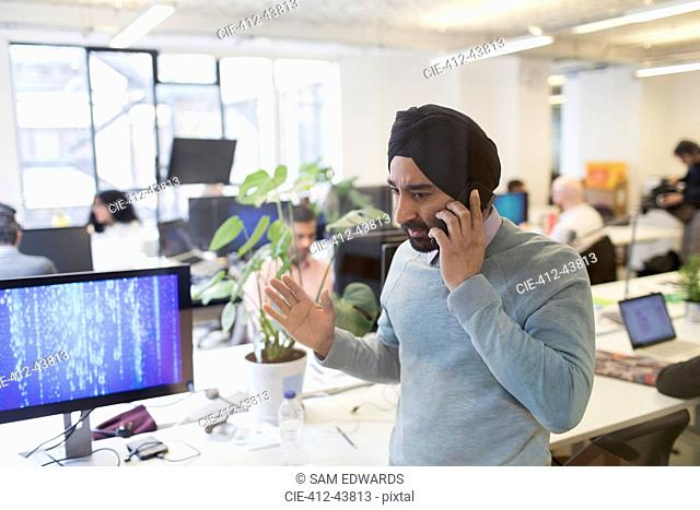 Indian computer programmer in turban talking on smart phone in office