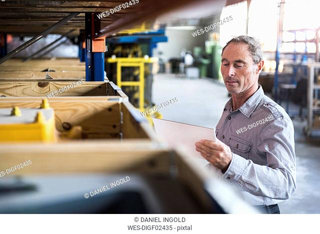 Man looking at tablet in industrial hall