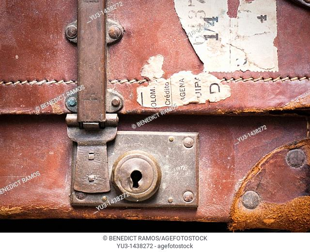 Detail of old brown leather suitcase with torn labels