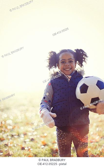 Portrait smiling girl with soccer ball in sunny autumn park