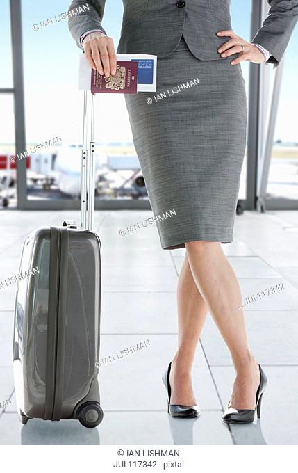 Businesswoman At Airport With Luggage And Passport