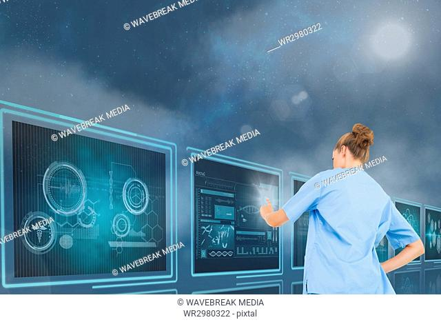 Woman doctor interacting with 3d medical interfaces against blue background with flares