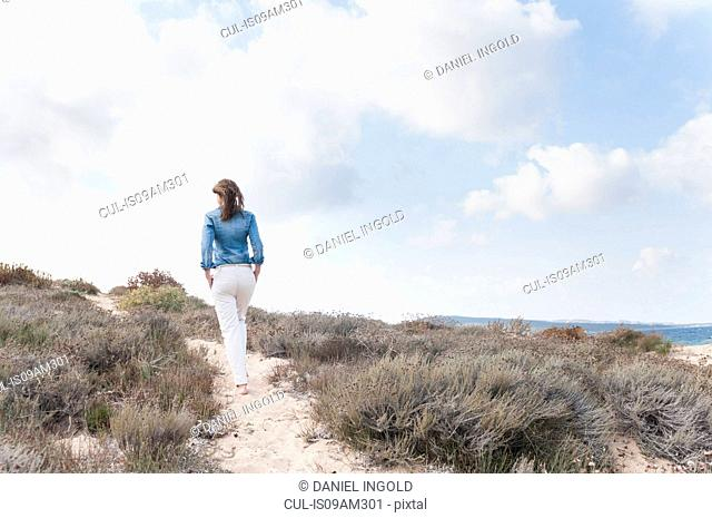 Rear view of mid adult woman strolling in sand dunes, Sardinia, Italy