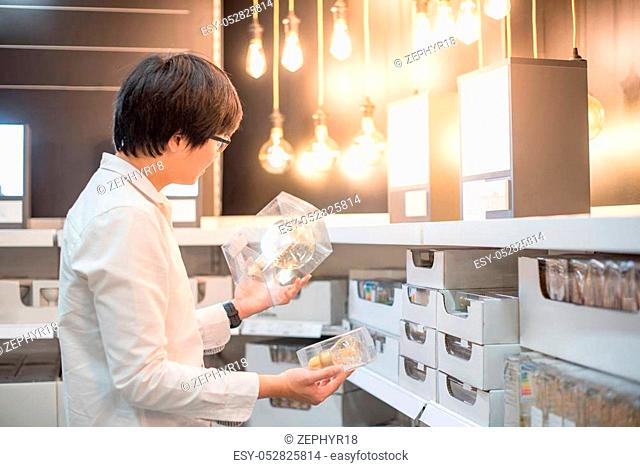 Young Asian man choosing package of electrical light bulb, furniture home decoration shopping concept