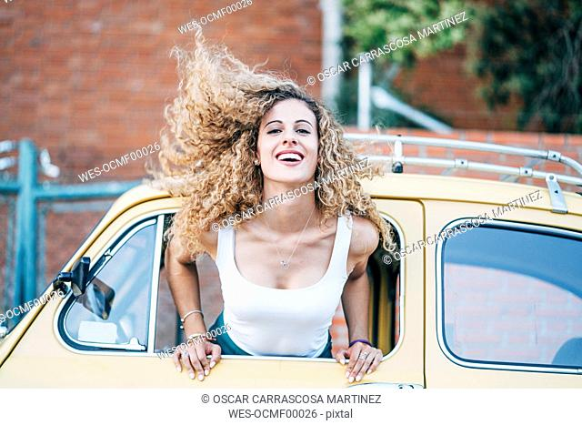 Portrait of blond woman leaning out of window of classic car tossing her hair
