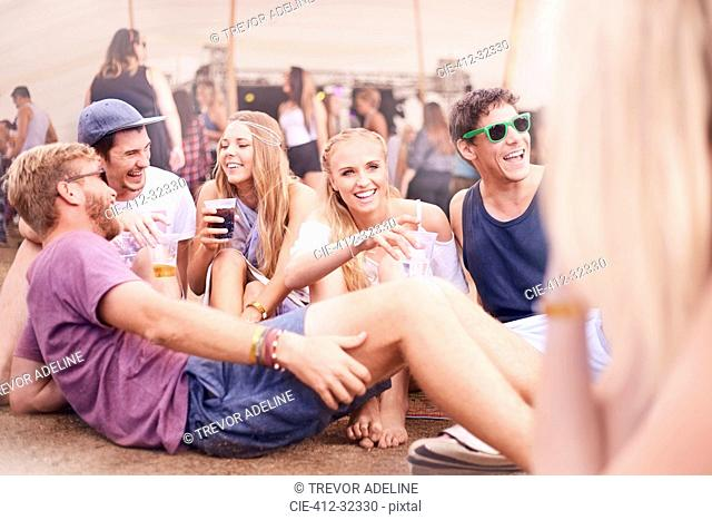 Young friends hanging out drinking and talking at music festival