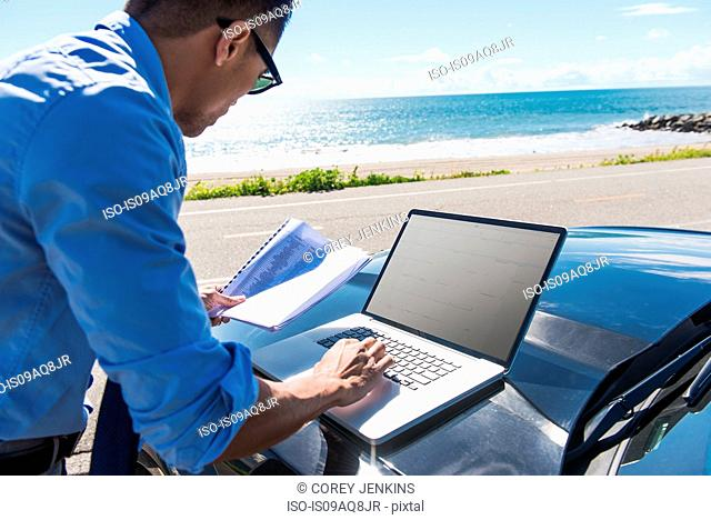 Young businessman at coast parking lot typing on laptop whilst reading paperwork