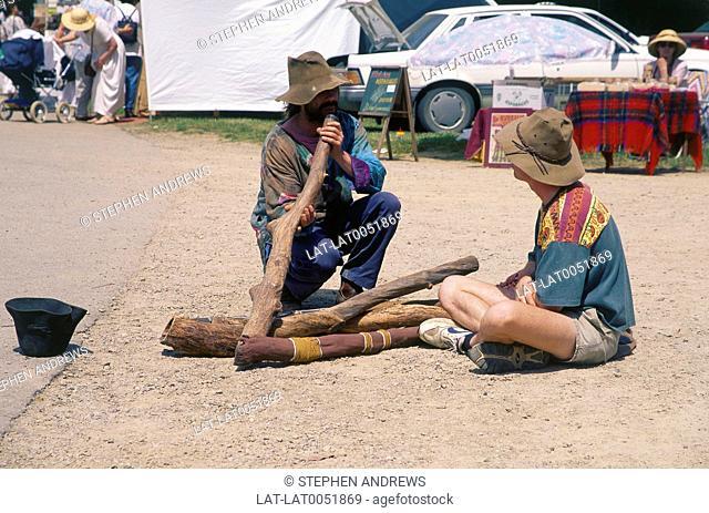 Aborigine playing wooden didgeridoo at craft market. Man sitting watching