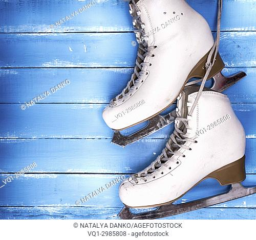 pair of worn white leather skates for figure skating on a blue wooden background, empty space on the left