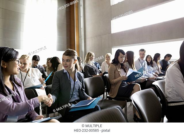 Students talking in lecture audience in auditorium