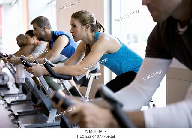 Focused woman on stationary bike in spin class