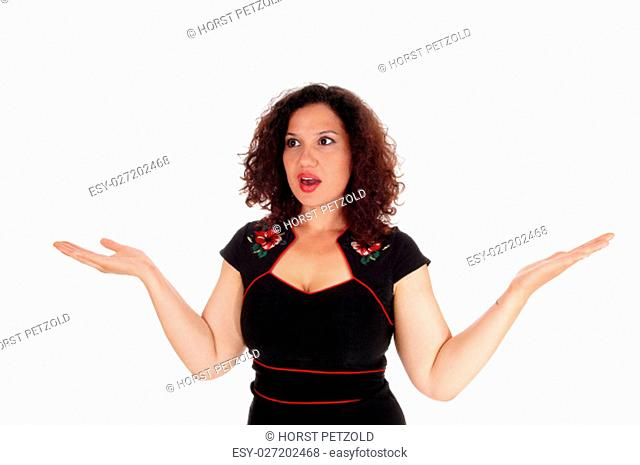 A beautiful young woman with curly brunette hair is frightened, holding.her hand to the side, isolated for white background.
