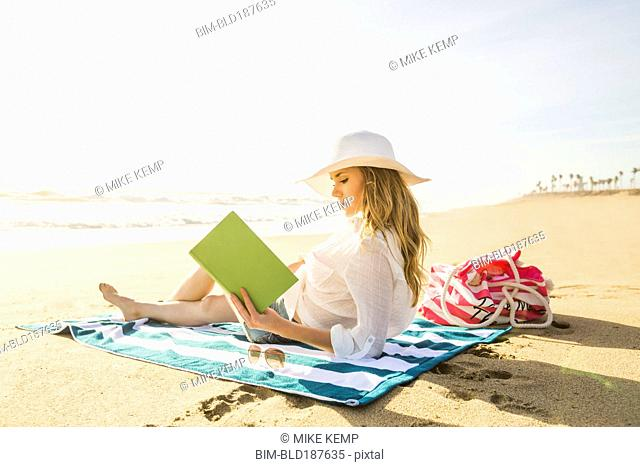 Caucasian woman reading book on beach