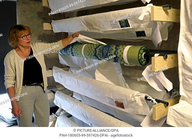 05 June 2018, Germany, Ludwigslust: Project director Dahl showing in one of the palace's attic rooms the newly woven silk damask fabrics and the trimmings for...
