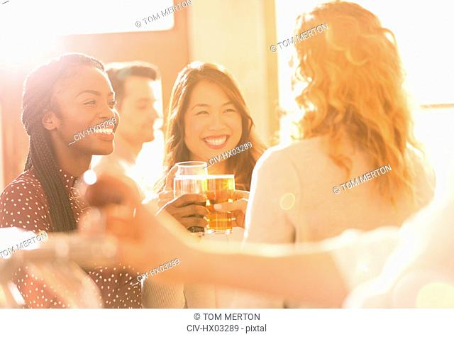 Smiling women friends toasting beer glasses in sunny bar