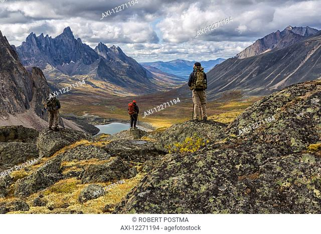 A group of hikers standing on rocks overlooking the colourful valleys in Tombstone Territorial Park in autumn; Yukon, Canada
