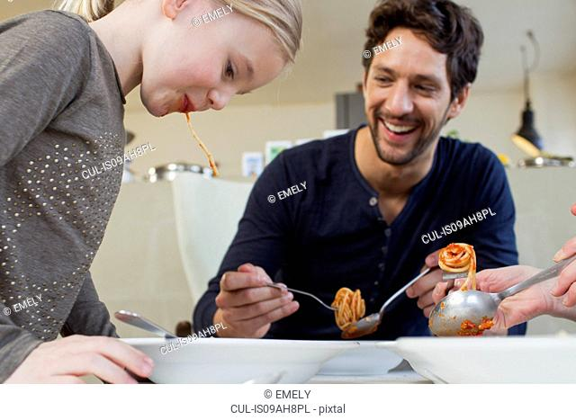 Mid adult man and family eating a spaghetti meal