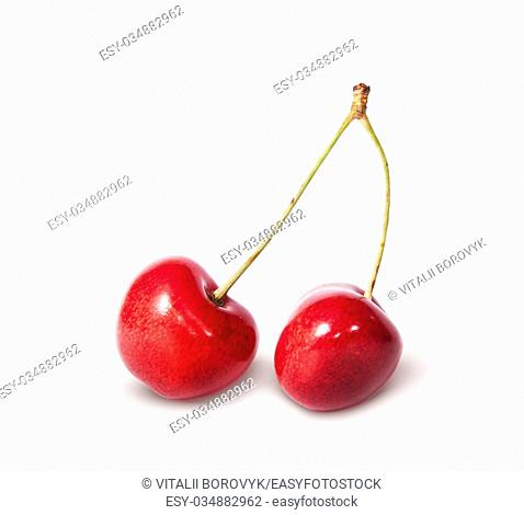 Two red juicy sweet cherries deployed isolated on white background