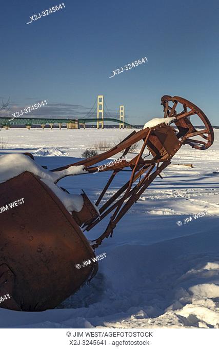 Mackinaw City, Michigan - A buoy on shore near the Mackinac Bridge crossing the frozen Straits of Mackinac. The straits connect Lake Michigan and Lake Huron