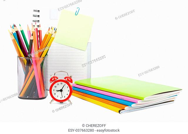Crayons with notebooks and alarm clock on isolated white background, front view