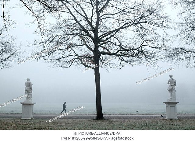 05 December 2018, Hessen, Kassel: A jogger walks past statues in the Karlsaue on a frosty and foggy morning. Photo: Uwe Zucchi/dpa