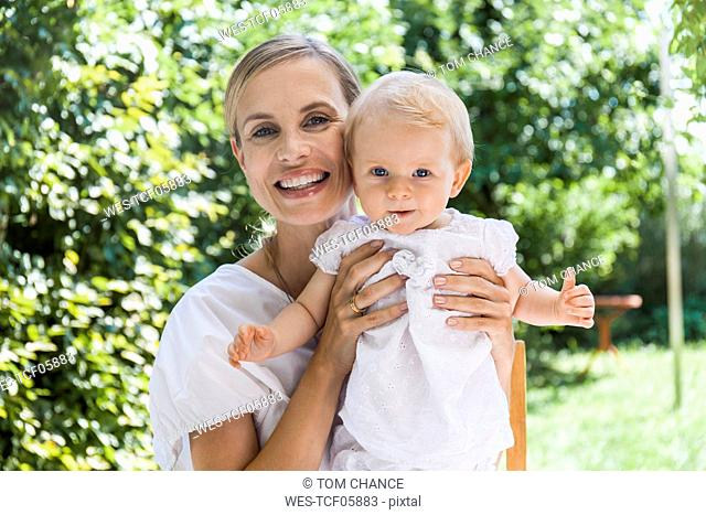 Portrait of happy mother holding her baby girl outdoors