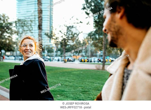 Smiling young woman turning round looking at boyfriend