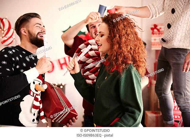 Young man and woman singing with pretend microphones at christmas party