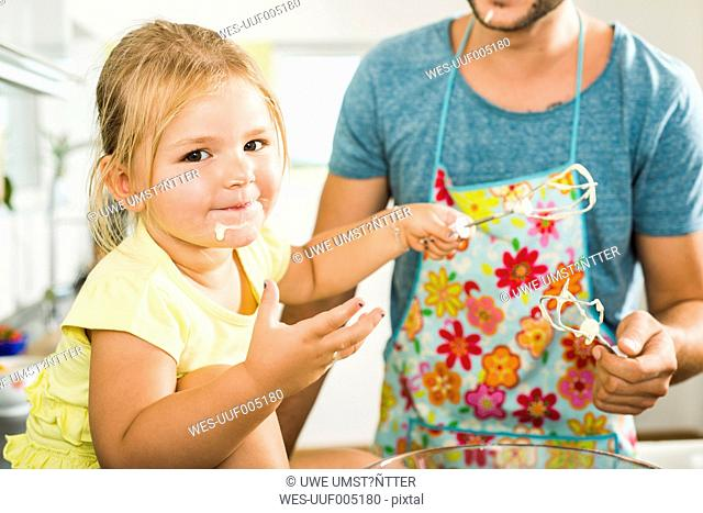 Portrait of girl baking with father in kitchen