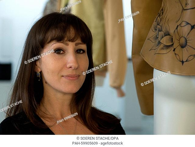 Munich-based fashion designer Nina Athanasiou poses between her creations at the 'Konzulat' venue during the opening of her vernissage and art installation...