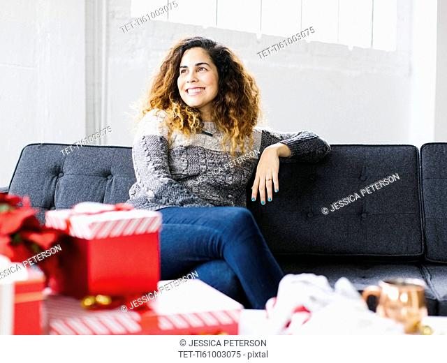 Happy woman on sofa with Christmas gifts in foreground