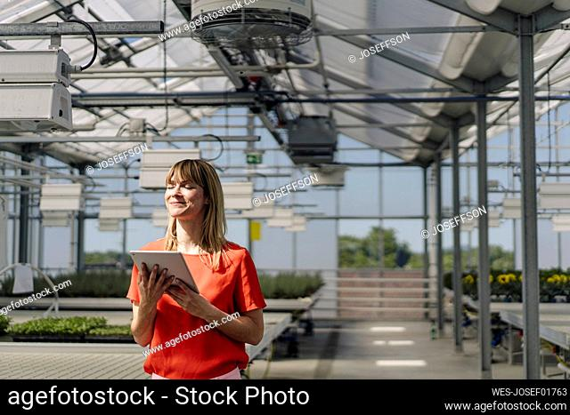Smiling female entrepreneur with eyes closed holding digital tablet while standing in greenhouse