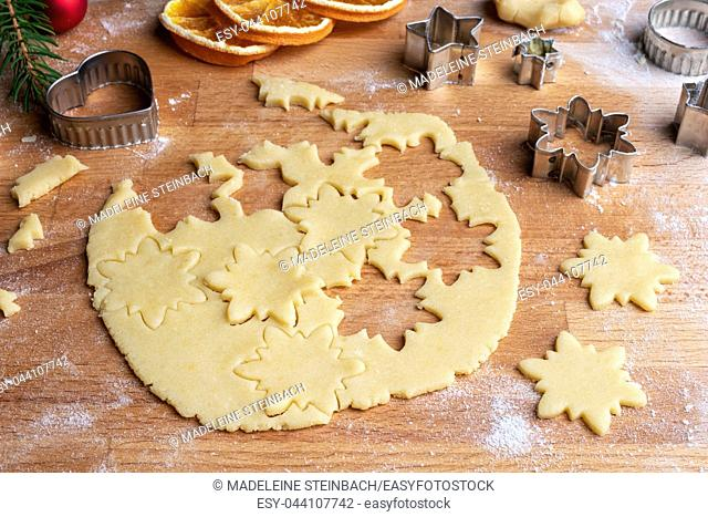 Cutting out star shapes from rolled out dough to prepare traditional Linzer Christmas cookies