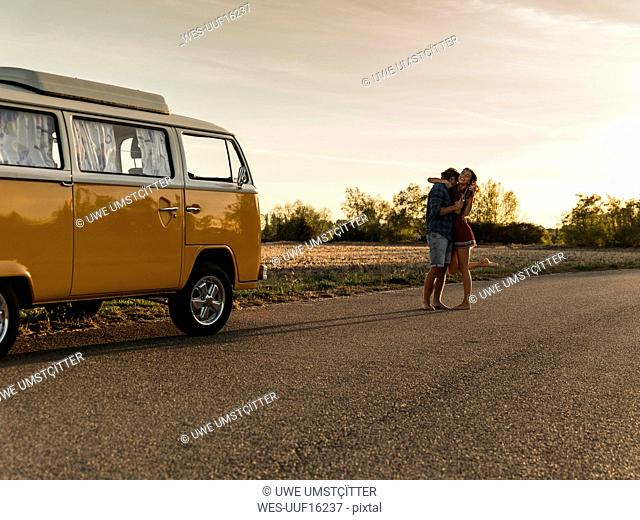 Happy couple doing a road trip with a camper, laughing and embracing on the road