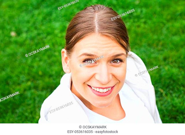 Young smiling female with sporty outfit relaxing in the park, outdoor