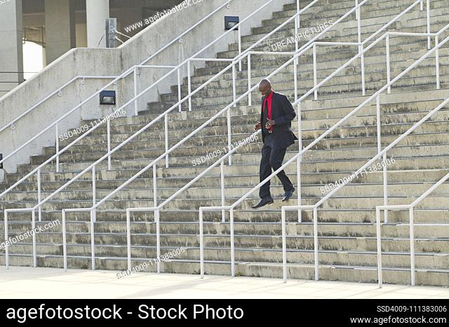 African American businessman descending stairs