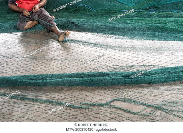 Fisherman repairing fishing net, Western Province, Sri Lanka
